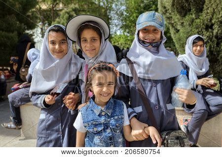 Fars Province Shiraz Iran - 19 april 2017: Several Iranian schoolgirls are posing for a photographer in the city center on a sunny day.