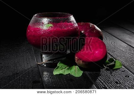 A close-up of a spacious glass with refreshing, blended vegetable smoothie on a black background. Sugar cut beetroot, beetroot leaves next to dairy healthful yogurt on a black wooden table.
