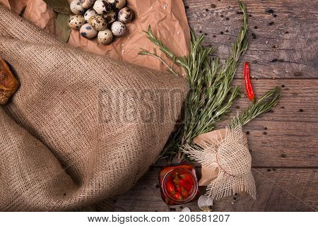 Top view of piquant red chili pepper in a glass jar, green atomatic twigs of rosemary and speckled quail eggs, grocery paper, table-cloth on a wooden table on a light wooden background.