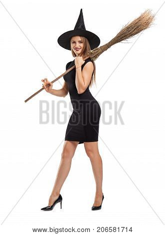 Stunning, gorgeous young witch holding a broom ready to fly away. Halloween witch girl in a black hat isolated on a white background.