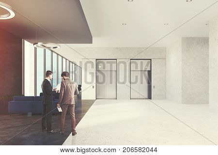 Office elevator hall with a waiting area dark blue sofas loft windows and round lamps. An open space room in the background. People. 3d rendering mock up toned image