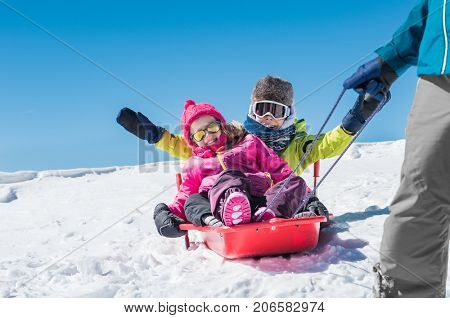 Father sledding his little son and daughter. Cute girl and happy boy being pulled on a red sled. Dad pulling his children in a bobsled on the snow. Winter vacation with family on snowy mountains.