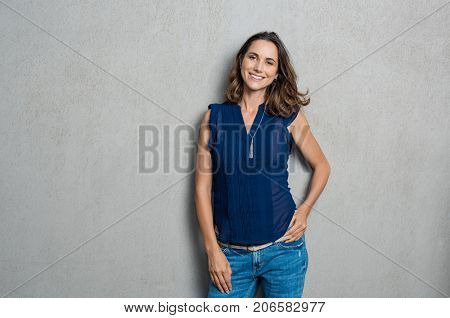 Portrait of cheerful mature woman standing against grey wall. Happy mid woman looking at camera against grey background with copy space. Smiling carefree latin woman looking at camera.