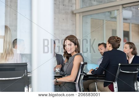 Young smiling business woman attending meeting in modern boardroom. Portrait of businesswoman looking at camera. Satisfied beautiful young woman sitting at conference table with team.