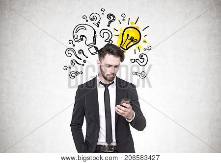 Close up portrait of a young bearded businessman wearing a dark suit and looking at his smartphone screen. Concrete wall background with question marks and a glowing light bulb