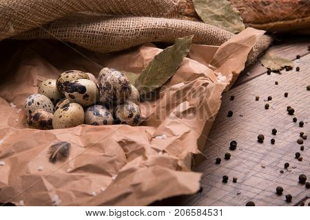Closeup of speckled quail eggs, dried bay leaves, different fragrant seasonings, a little bird feather, grocery paper, ingredients for tasty dishes on a light, wooden background.