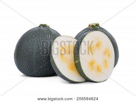Two whole fresh zucchini and slices with yellow seeds, isolated on a white background. Slices of natural and organic dark green zucchini, close-up. Summer ingredients. Copy space.