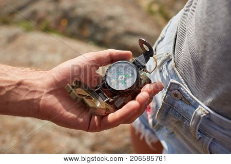 Hand with compass at mountain road at sunset sky. Searching direction with a compass in summer mountains. Close-up view of hand showing little round compass to camera, with incognito man.