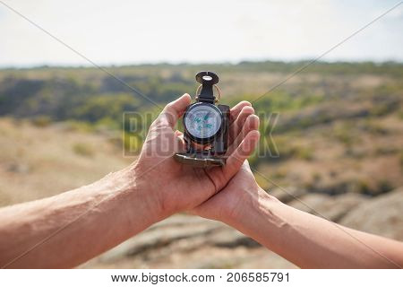 Hand with compass at mountain road at sunset sky. Searching direction with a compass in summer mountains. Close-up view of hand showing little round compass to camera, with incognito man. poster