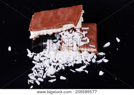 Homemade chocolate coconut bars with coconut flakes on top.