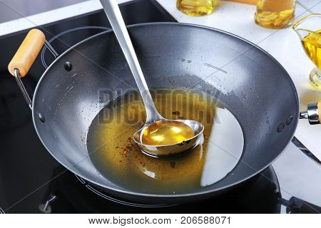 Wok with used vegetable oil and ladle on stove
