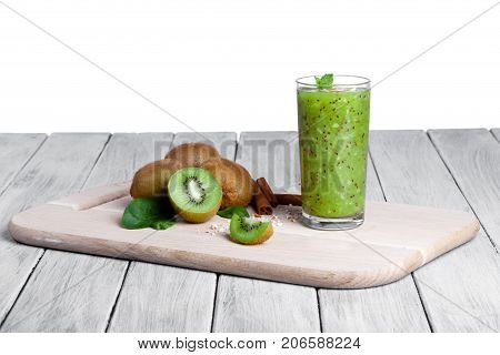 Kiwi fruits full of nutritious vitamins, cinnamon sticks and walnuts on a wooden table, isolated on a white background. A smoothie from juicy kiwi, grated nuts, and mint on a cutting board.
