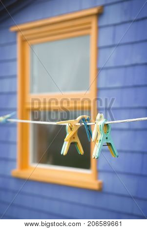 Green and yellow clothespins on a line in front of a yellow window on a purple wall