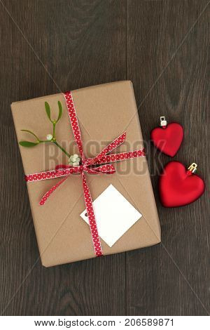 Christmas gift box wrapped in brown paper, tag, red ribbon with mistletoe, heart shaped bauble decorations on oak background. Top view xmas and holiday love concept.