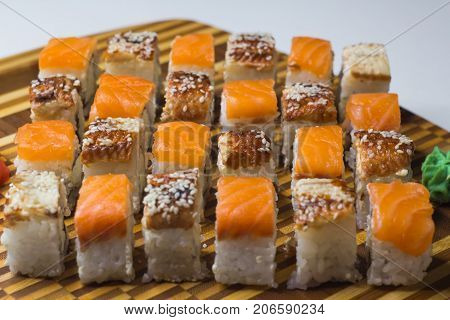 The set of rolls with ginger and wassabi on bamboo board. Unagi rolls and philadelphia rolls. Focus on middle line.