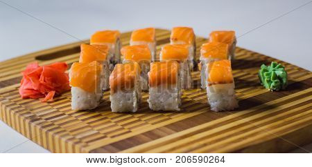 The set of salmon rolls on bamboo board with ginger and wasabi.