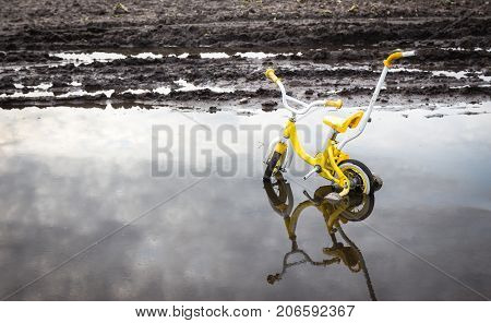horizontal image of a broken yellow Child's bike stuck in a pool of water.