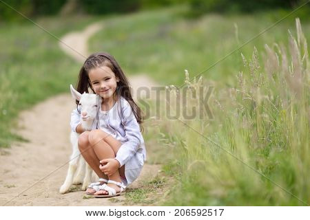 Little girl plays and hgs goatling in country, spring or summer nature outdoor. Cute kid with baby animal, countryside outdoor portrait, forest, glade background. Friendship of child and yeanling