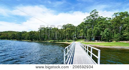 Waterfront landscape with a jetty blue sky white cloud and a tree studed horizon over water. Lake Macquarie Central Coast New South Wales Australia.