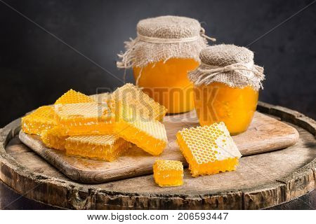 Jars of honey and honeycombs on a wooden barrel on a dark background