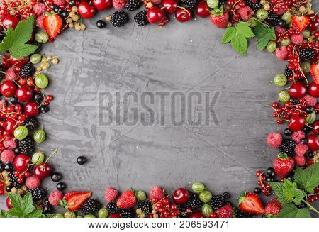 Frame of ripe berries from a garden with leaves on a stone plate. Mix of strawberries, currants, blackberries, cherries. Top view
