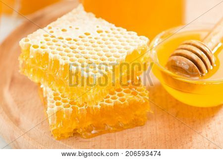Fresh pieces of honeycomb with honey on a wooden board