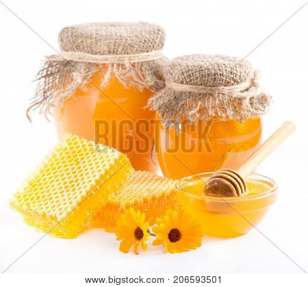 Flower honey in a jar and honeycomb on a white background