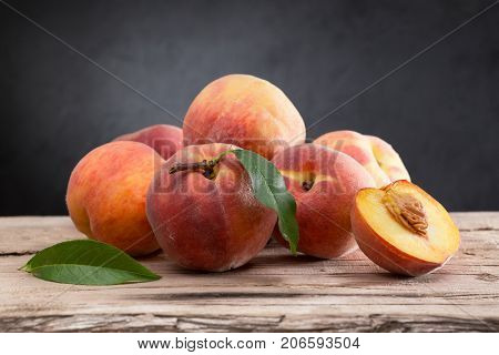 Ripe peaches on a wooden board on a dark background