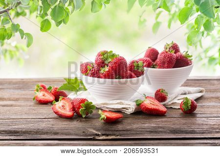 Ripe strawberries in white plates on a wooden table on a background of green leaves