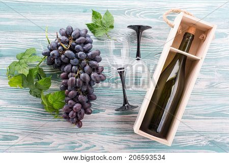 Bunch of grapes and a bottle of wine on a wooden background. Top view