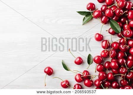 View from above. Cherry with leaves on a wooden board. view from above