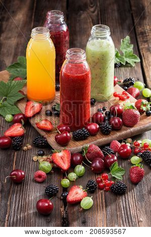 Homemade refreshing fruit vitamin drink. Colored smoothies from berries on a wooden board