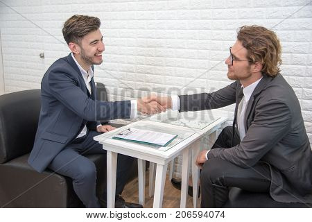 Two businessmen shake hand for contact and startup new project together on sofa indoors Business and New project launch contact agreement concept