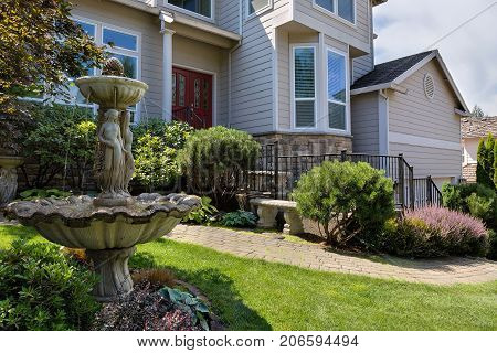 Residential single home in North America suburbs frontyard with manicured garden green lawn paver brick walkway bench and stone water fountain