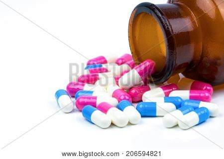 Colorful of antibiotic capsules pills with amber glass bottle isolated on white background. Drug resistance antibiotic drug use with reasonable health policy and health insurance concept.