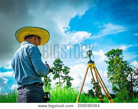 Asian smart engineer or surveyor in black jeans and long sleeve shirt and woven bamboo hat. He is working on controller screen for surveying land in rice field Thailand. GPS surveying instrument.
