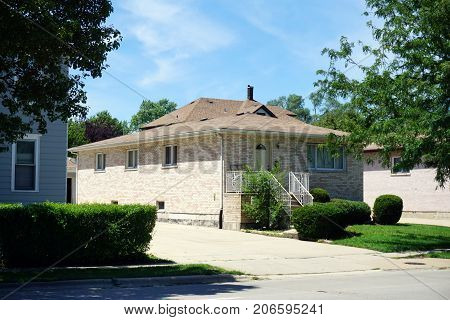 JOLIET, ILLINOIS / UNITED STATES - JULY 25, 2017: A single family brick home on Broadway Street, in one of Joliet's less affluent neighborhoods.