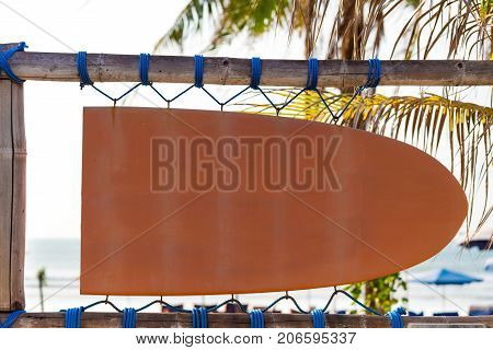 Blank orange vintage signboard in shape of surf board with copy space and palm tree in background. Vacation and travel concept