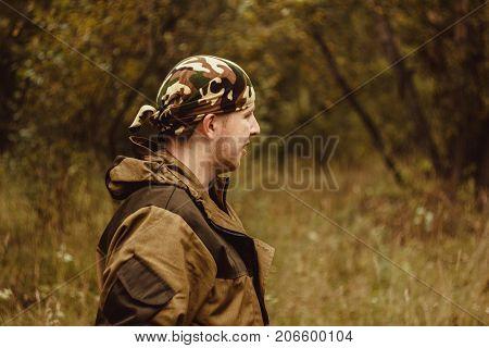 man military bandana standing in the woods