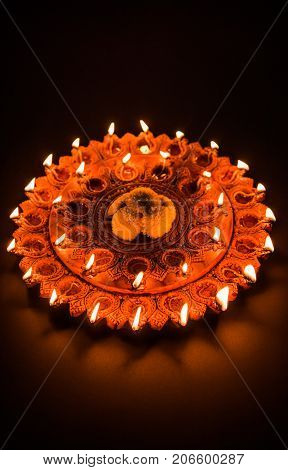 Stock Photo of an illuminated terra-cotta Diwali lamp or Diya with detailed artwork on it. on a moody background and selective focus