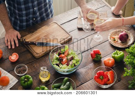 Couple Drinking Wine While Cooking Dinner In Kitchen
