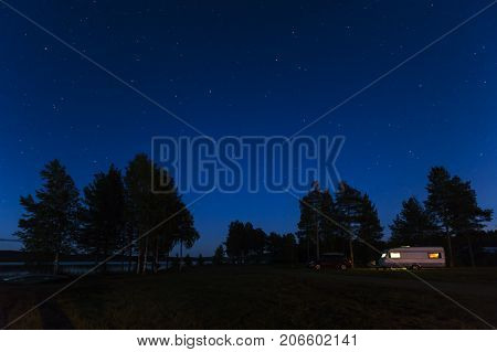 LAPLAND, SWEDEN ON SEPTEMBER 01. Night view of trees in silhouette, caravan, car and bright stars on September 01, 2017 in Lapland, Sweden.  Lights on in the caravan. Editorial use.
