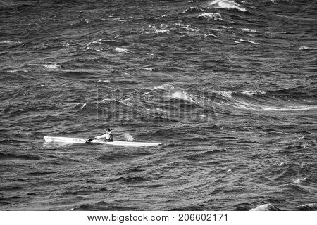An ocean kayak paddler heads downwind in wild windy conditions on his surfski.