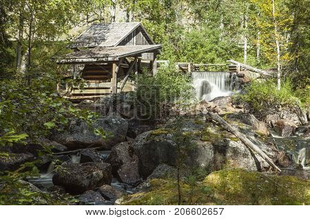 LAPLAND, SWEDEN ON SEPTEMBER 03. View of an old wooden water mill in a creek, brook on September 03, 2017 in Lapland, Sweden. Boulders, dam and wilderness. Editorial use.