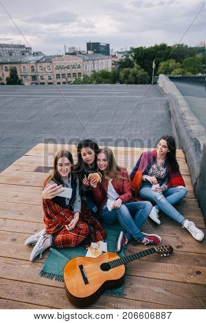 Selfie in meeting close friends. Smiling girls with fast food make self-portrait by smartphone, unusual places for rest and communication, sharing time together, cheerful and joyful atmosphere concept