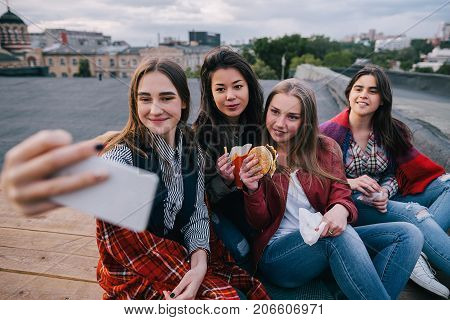 Selfie in meeting close friends, close up. Smiling girls with fast food make self-portrait by smartphone, unusual places for rest and communication, sharing time together, cheerful atmosphere concept