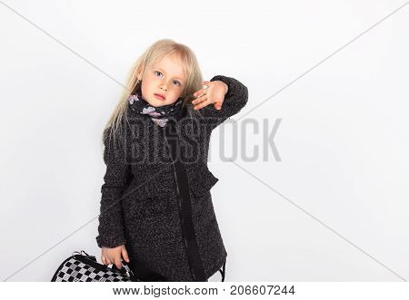 Adorable Little Girl In A Coat And With A Suitcase, On A White