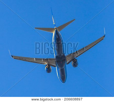 Bologna, Italy - December 20, 2016: Ryanair blue commercial airplane close up isolated against the blue sky, taking off behind view. Ryanair is main european low cost flights company