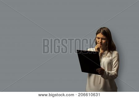 portrait of a young beautiful student girl carefully looks at the information on clipboard. isolated on gray.