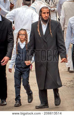 The father leads the son by the hand. The Hasidim pilgrims. Uman Ukraine - 21 September 2017: Rosh Hashanah Jewish New Year.
